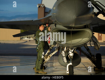 Captain Jake Pippenger, 54th Fighter Group pilot, inspects an F-16 Fighting Falcon to prepare for a training sortie - Stock Photo