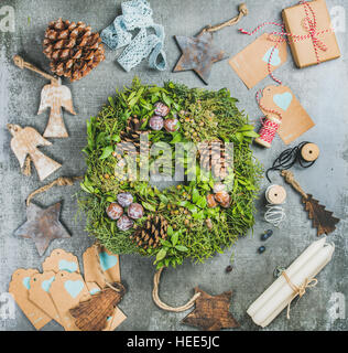 Christmas green wreath, pine cones, wooden toys, candles, decorative materials - Stock Photo