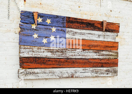 Painted American flag on wood hanging on the exterior of a building in south central Alabama USA. - Stock Photo