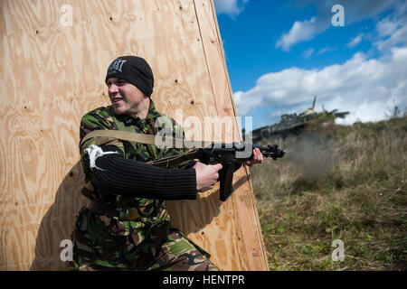 A Ukrainian military cadet acting as a simulated opposing force fires his rifle during a simulated high value target - Stock Photo
