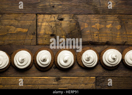 Hot chocolate cookies with marshmallow meringue on dark brown rustic wood background - Stock Photo