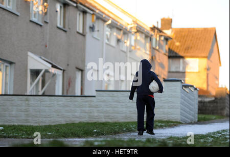 A boy walks on a snow covered path on the Gurnos Council housing estate in Merthyr Tydfil, South Wales, UK. - Stock Photo