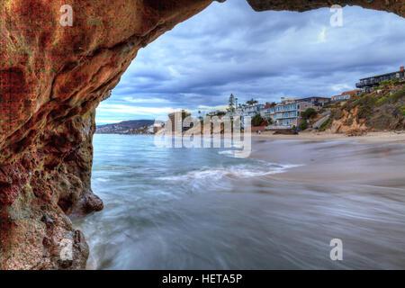 Sunset hits homes along Pearl Street Beach through a rock keyhole in Laguna Beach, California, USA - Stock Photo