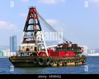 A lighter is a type of flat-bottomed barge used to transfer goods and passengers to and from moored ships. Hong - Stock Photo