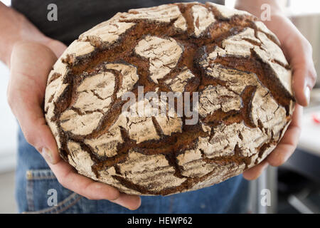 Cropped view of man holding freshly baked bread - Stock Photo