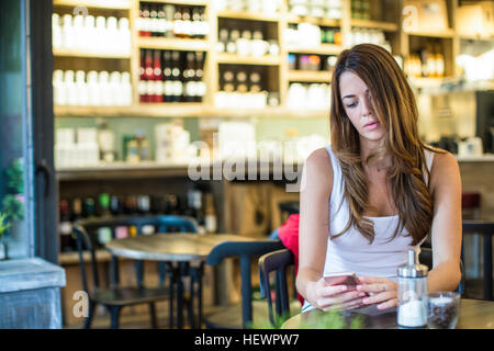 Young woman sitting in cafe reading smartphone texts - Stock Photo