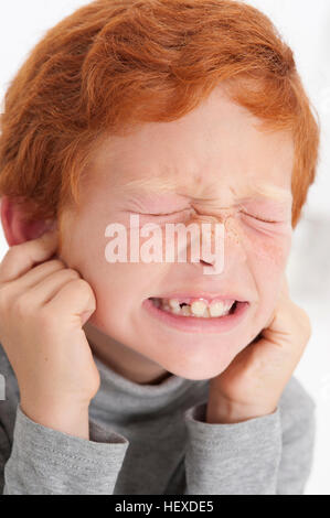 MODEL RELEASED. Boy putting fingers in ears with eyes closed. - Stock Photo