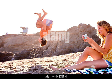 Young man on the beach doing a somersault with woman checking cell phone - Stock Photo