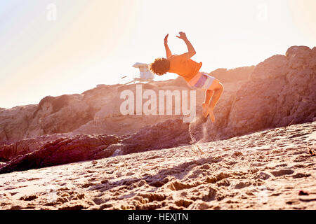 Young man on the beach doing a somersault - Stock Photo