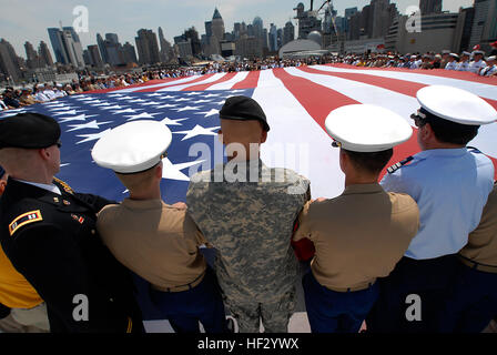 Members of the Fleet Week flag detail unfurl a U.S. flag during a Memorial Day commemoration aboard the USS Intrepid - Stock Photo