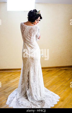 Beautiful bride in white lace dress and flowers in hair. Waiting in white room for her groom. Wedding morning. - Stock Photo