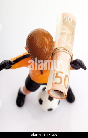 Football player with rolled-up 50-Euro bill: football bribes - Stock Photo