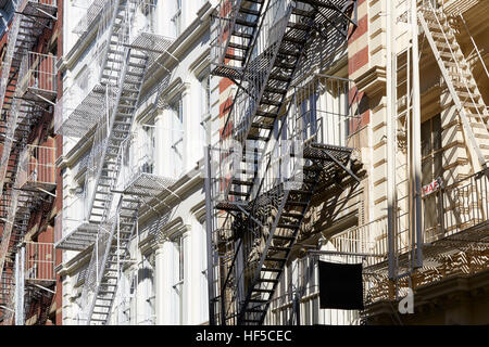 Houses facades with fire escape stairs, sunny day in Soho, New York background - Stock Photo