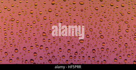 Water drops on a metallic surface with a pink to orange and yellow gradient - Stock Photo