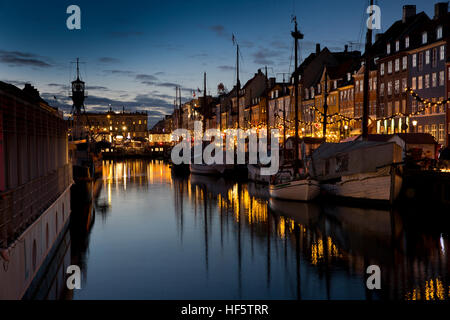 Denmark, Copenhagen, Nyhavn, winter, boats moored at quayside at night, reflected in water - Stock Photo