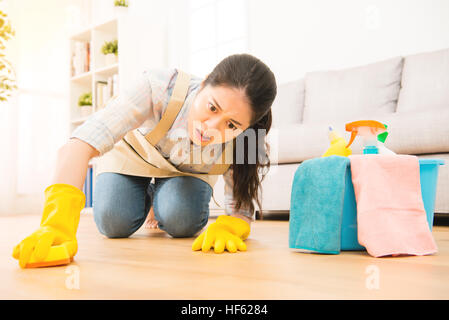 housewife scrub hardly cleaning floor in protective gloves with struggle face expression kneeling on wooden ground - Stock Photo