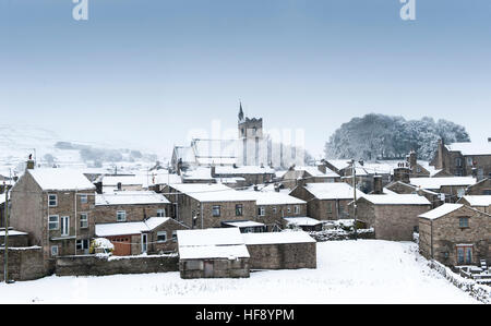 Hawes, North Yorkshire, with the church of St Margarets on the skyline, covered in the first snow of the winter. - Stock Photo