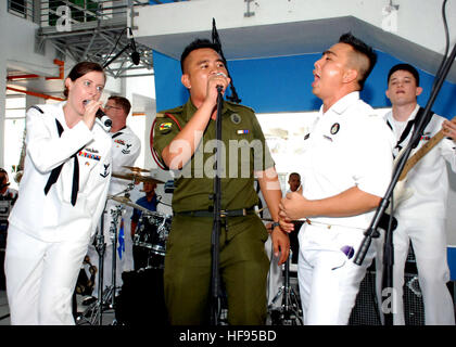 Petty Officer 3rd Class Nina Church, assigned to the U.S. 7th Fleet Band ensemble, Orient Express, joins two musicians - Stock Photo