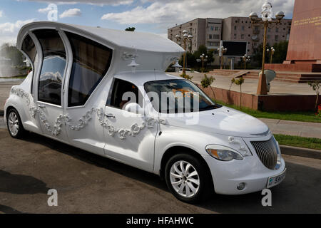 Elaborate limousine made to look like a carriage for a wedding party at Ordabassy square fountain Shymkent Kazakhstan - Stock Photo