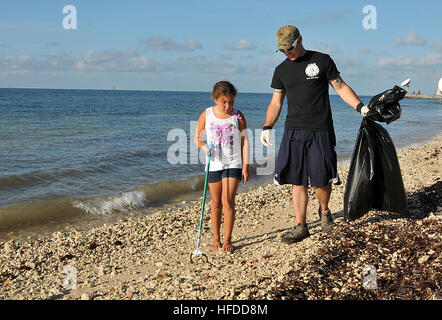 U.S. Navy Master-at-Arms 2nd Class Justin Sosa and his daughter look for trash to pick up at Truman Annex at Naval - Stock Photo