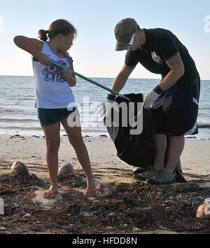 U.S. Navy Master-at-Arms 2nd Class Justin Sosa and his daughter pick up trash at Truman Annex at Naval Air Station - Stock Photo