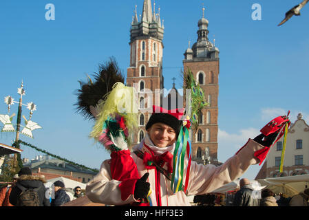 Man dressed in colourful costume with St Mary's Church Market Square Krakow Poland - Stock Photo