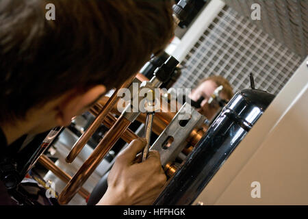 engineers assemble refrigeration compressors in industrial warehouse - Stock Photo