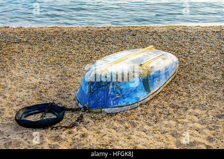Derelict blue colored boat on a shingle beach with sea in the background. Photo taken at Shoeburyness near Southend - Stock Photo