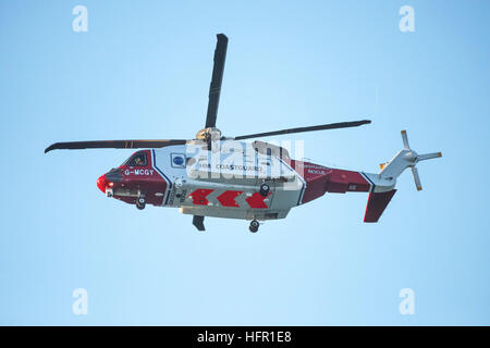 A Sikorsky S-92A HM Coastguard SAR Helicopter G-MCGY operated by Bristol Helicopters flies overhead on the North - Stock Photo
