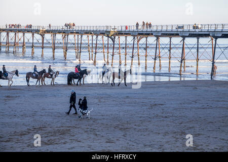 People exercising their horses  and dogs on the beach at Saltburn by the Sea on the north east coast of England - Stock Photo