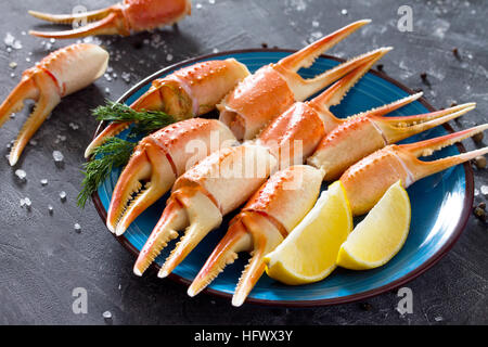 Cooked crab claws with lemon, sea salt and pepper on a concrete background. - Stock Photo