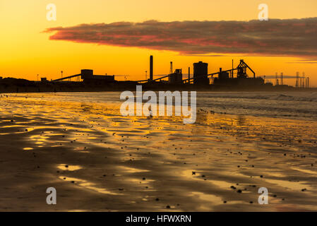 Redcar steelworks in silhouette at sunset - Stock Photo