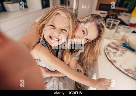 Smiling little girl and woman in kitchen taking selfie. Happy young mother and daughter cooking food. - Stock Photo
