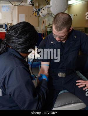 U.S. Navy Hospital Corpsman 2nd Class Porsche Giles, left, draws blood from Culinary Specialist 3rd Class Ronald - Stock Photo