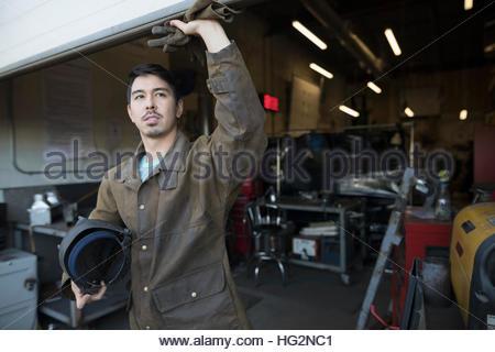 Male welder standing at workshop doorway - Stock Photo