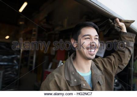 Portrait smiling male welder at workshop doorway - Stock Photo