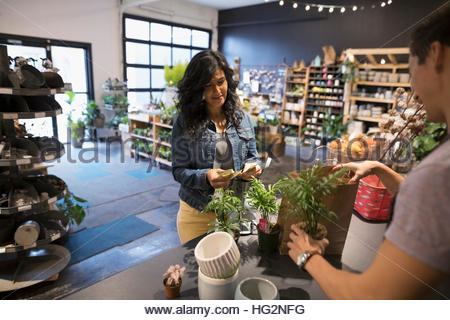 Male shop owner helping female customer buying plants at shop counter - Stock Photo