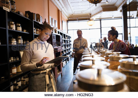 Female spice shop owner using digital tablet in shop - Stock Photo