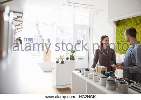 Male shop owner helping female customer browsing candles in home fragrance shop - Stock Photo