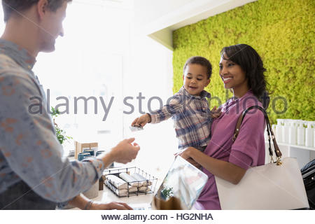 Mother with son paying male shop owner with credit card at counter in home fragrances shop - Stock Photo