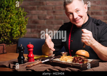 Happy man eating burger in restaurant - Stock Photo