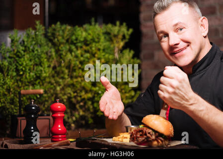 Joyful man eating burger and French fries in restaurant - Stock Photo