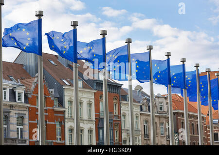 A line of EU flags flying on metal poles in front of the Berlaymont Building in Brussels with traditional houses - Stock Photo