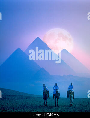 Full moon rising behind the Pyramids at dusk, Giza, Cairo, Egypt - Stock Photo