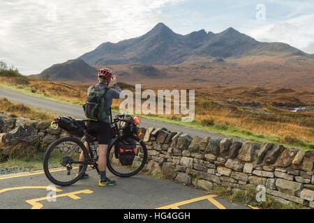 Isle of Skye, Scotland, UK - a cyclist takes a photograph of Sgurr nan Gillean in Glen Sligachan with phone - Stock Photo