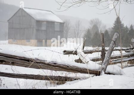 An ontario bank barn with split cedar rail fence in the snow in winter - Stock Photo
