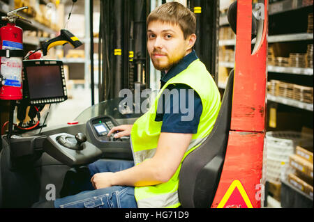 man driver Reachtruck busy working logistics warehouse store - Stock Photo