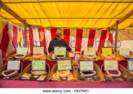 A vendor selling foodstuffs at a monthly flea market at Toji Temple. - Stock Photo