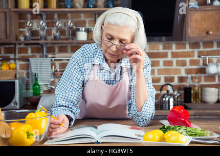 Serious senior woman looking in cookbook while sitting in kitchen - Stock Photo