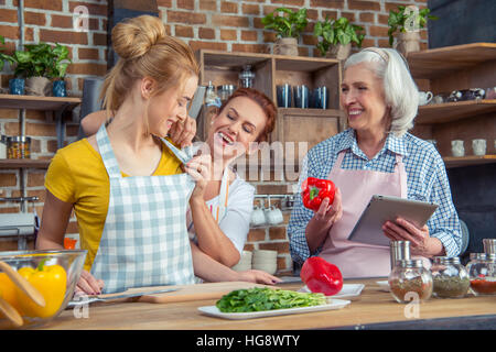 Smiling family cooking together in kitchen - Stock Photo